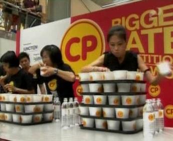 Kiirõgimise võistluse osalejad ja neile ette antud toidukuhjad. Osalejad on Aasias, kus tavaliselt ei liialdatud toiduga. Ma ei tea, mitu portsionit kräppi võitja alla kugistas. Kaader 10. mai 2010 Reporterist