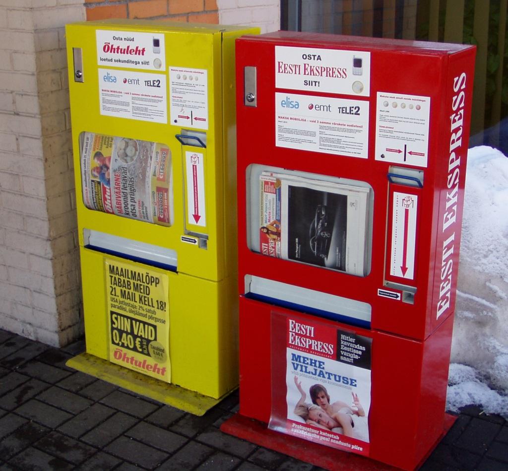 Kollane on Õhtulehe automaat ja punane Eesti Ekspressi oma. Ostu saab sooritada müntide eest või mobiilimaksega. Foto Virgo Kruve